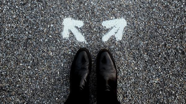 Illustrasjonsbilde av et par ben med svarte sko med to hvite piler overfor som peker i to forskjellige retninger tegnet på en mørk vei, tatt av Jon Tyson fra Unsplash