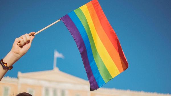 En hånd som holder et regnbueflagg