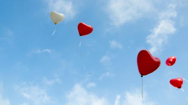 Illustrasjonsbilde av røde ballonger som flyger i himmelen, tatt av Christopher Beloch fra Unsplash