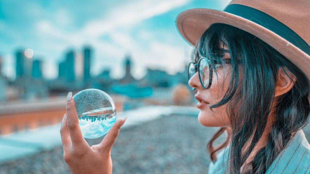 Illustrasjonsbilde av en kvinne med briller og hatt som holder en gjennomsiktig ball som reflekterer bybilde i bakgrunnen. Bilde tatt av Maryna Yazbeck fra Unsplash