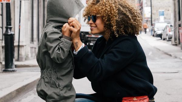 Illustrasjonsbilde av en mor med svart kåpe og solbriller som holder hendene til et lite barn i grå dress og smiler. Bakgrunnen er et bybilde. Illustrasjonsbilde tatt av Sai De Silva fra Unsplash