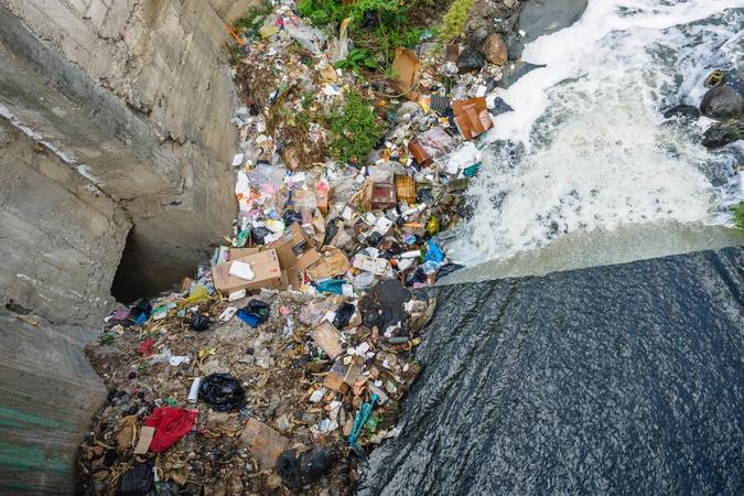 Illustrasjonsbilde av søppel ved siden av en elv, tatt av Alexander Schimmeck fra Unsplash