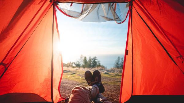 Bilde av et rødt telt med en person som ligger å ser på utsikt i skogen. Illustrasjonsbilde tatt av Will Truettner fra Unsplash
