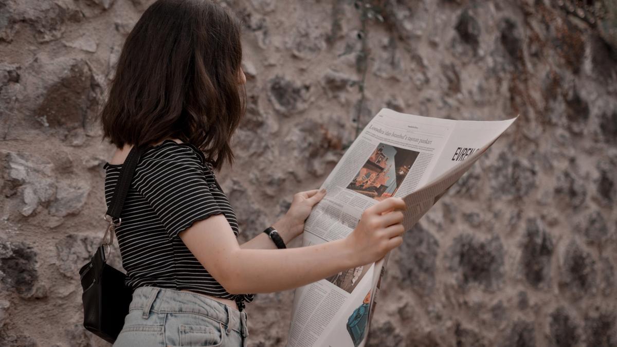 Illustrasjonsbilde av en kvinne som leser avisen tatt av Ekrulila fra Unsplash