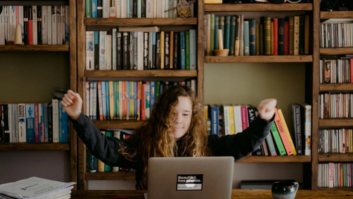Bilde av en jente som feirer noe foran en laptop. Bilde tatt av Annie Spratt fra Unsplash