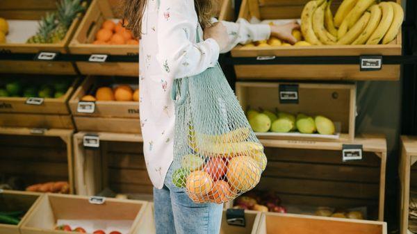Bilde av en kvinne på en zero waste matbutikk med frukt i et plastfritt handlenett