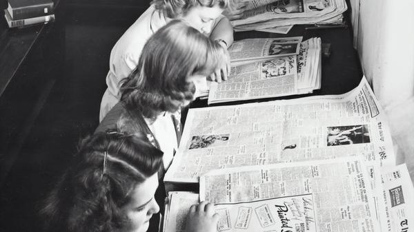 Kvinner sitter å leser avisen. Illustrasjonsbilde tatt av Museums Victoria fra Unsplash