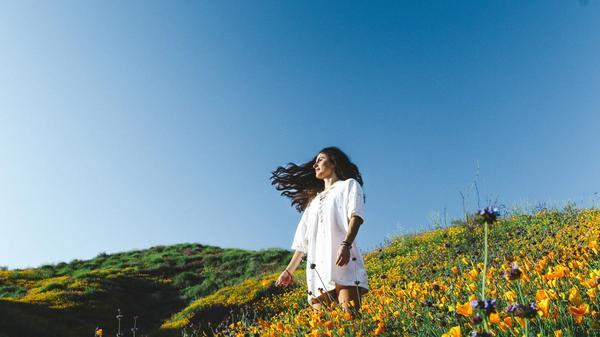 Jente som står i en blomstereng