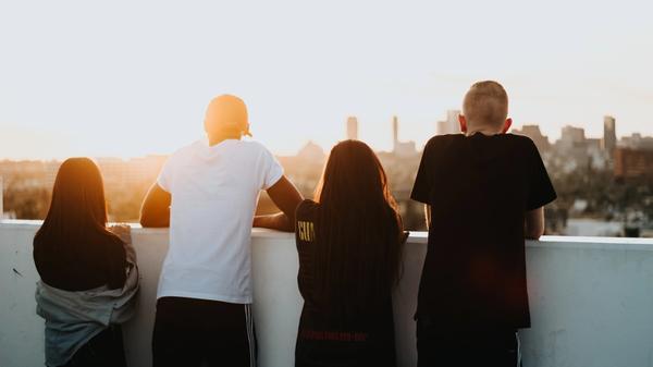 Fire venner på en takterasse som ser utover byen