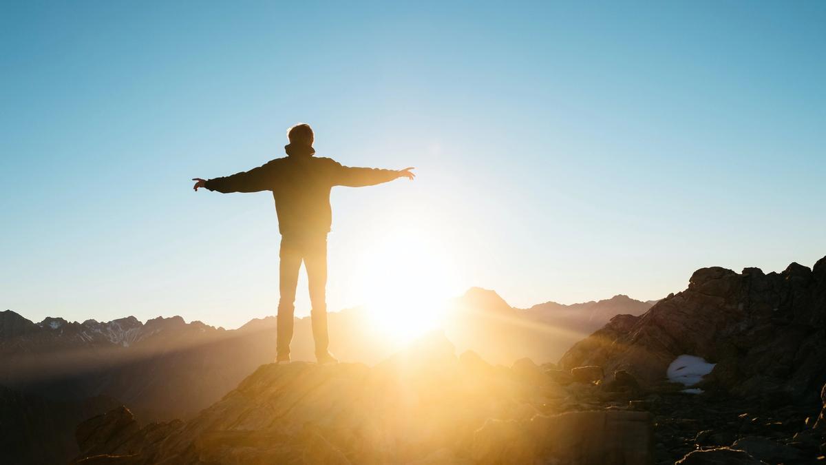 Illustrasjonsbilde av en mann som har armene ut mens han står å ser utover et fjell-landskap og en solnedgang. Bildet er tatt av Pablo Heimplatz fra Unsplash
