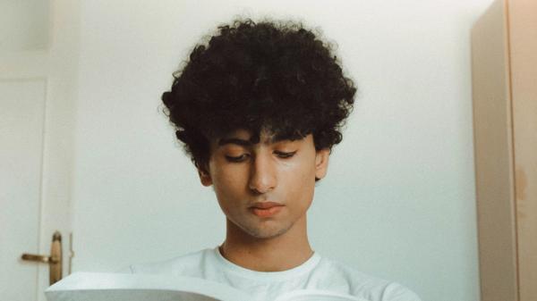 Ung mann leser en bok