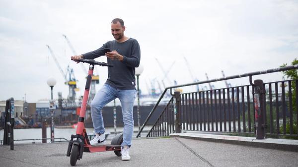 Illustrasjonsbilde av en mann som står og holder en e-sparkesykkel og bruker mobiltelefonen sin, tatt av Christina Spinnen fra Unsplash