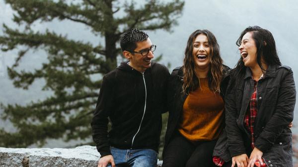 Tre venner sitter ute i regnet og ler sammen