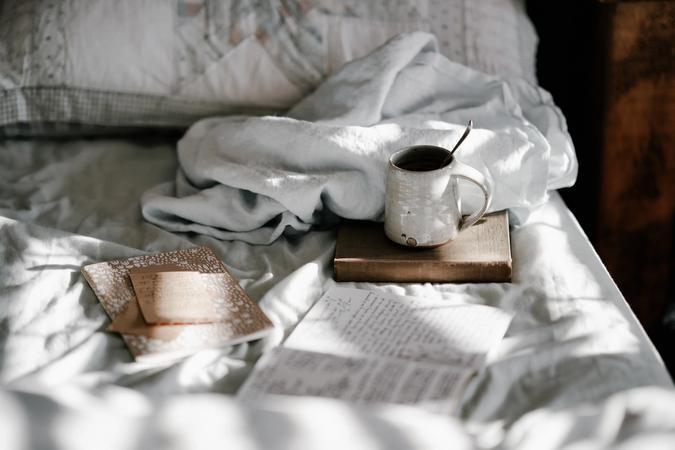 Illustrasjonsbilde av en seng med notatbøker og en kopp noe varmt å drikke. Bilde er tatt av Annie Spratt fra Unsplash