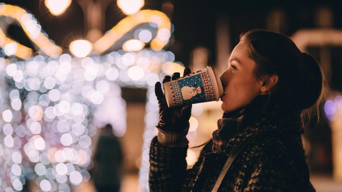Kvinne drikker fra ett julepappbeger ute omringet av julelyst