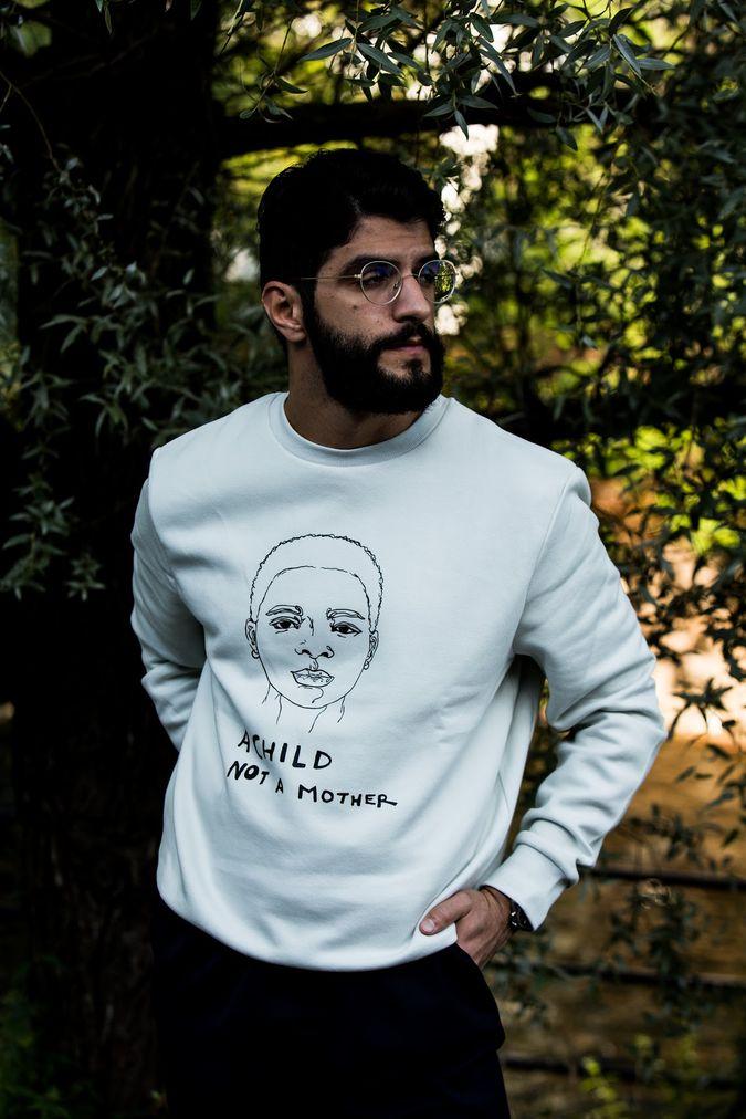 Mann som har på seg en hvit genser med motiv av en jente