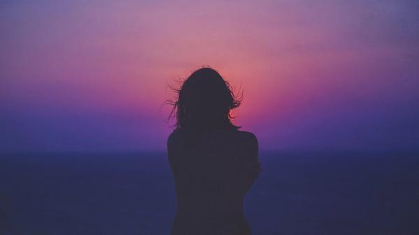 En jente som ser solen går ned i horisonten