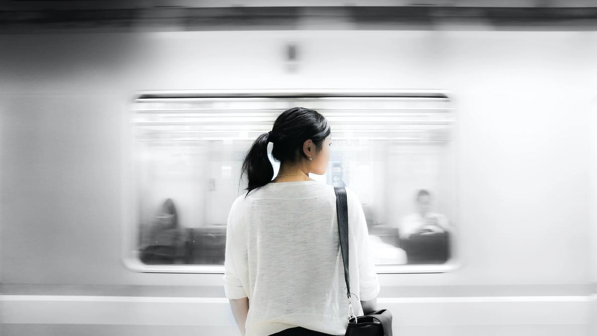Illustrasjonsbilde av kvinne med mørkt hår som står og ser på en t-bane som går fort forbi, tatt av Eutah Mizushima fra Unsplash