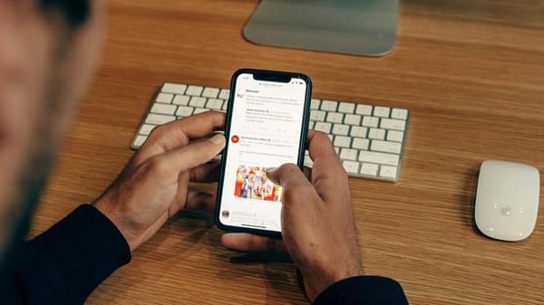 Illustrasjonsbilde av en mann som leser nyheter på en mobil, tatt av Charles Deluvio fra Unsplash