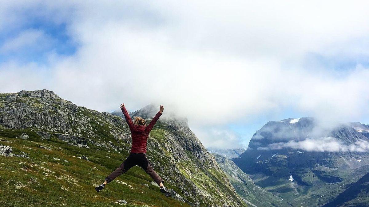 Kvinne som hopper på fjellet. Blå himmel med skyer bak grønne fjell. Bilde privat, Tine Norderhaug