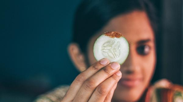Foto av en kvinne som holder en skive agurk