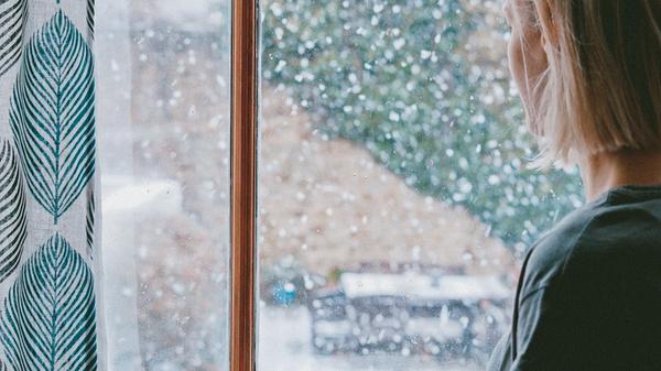 Kvinne ser ut vinduet med en kaffikopp