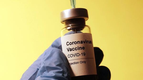 Illustrasjonsbilde av en COVID-19 vaksine som blir holdt av hender med blå hansker tatt av Hakan Nural fra Unsplash