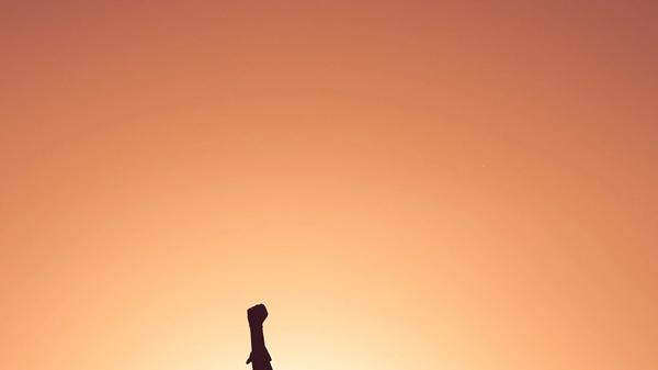 Kvinne som står med en arm opp i været med gul bakgrunn. Illustrasjonsbilde tatt av Miguel Bruna fra Unsplash