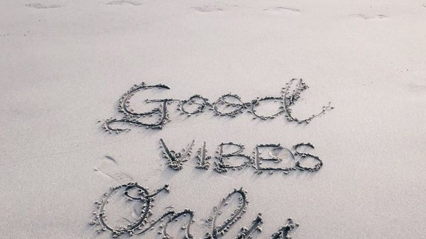 """good vibes only"" written in the sand at a beach"