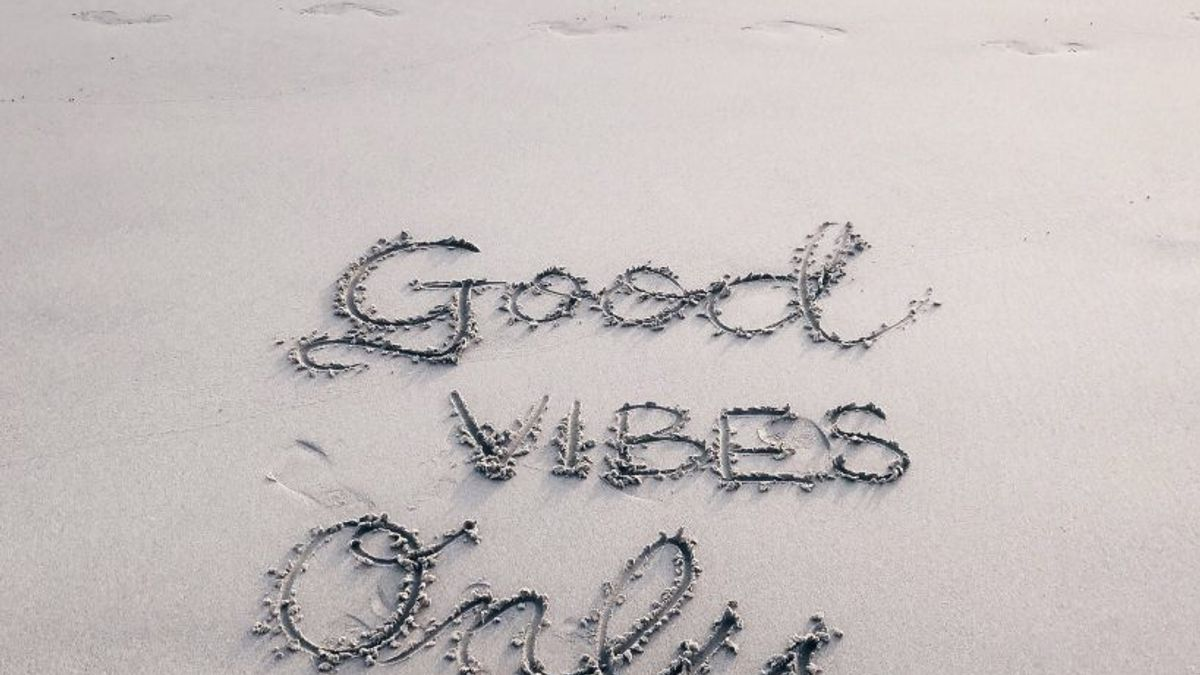 """""""good vibes only"""" written in the sand at a beach"""