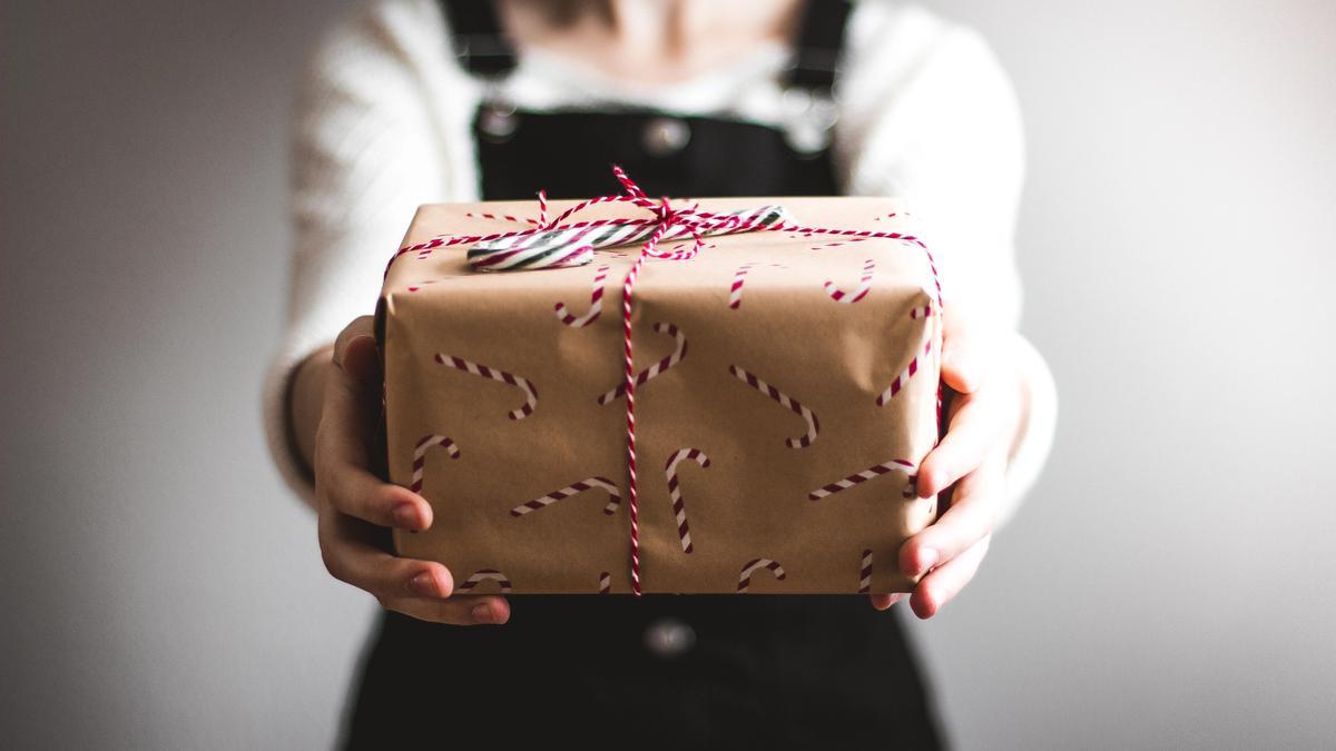 Kvinne holder frem en julegave