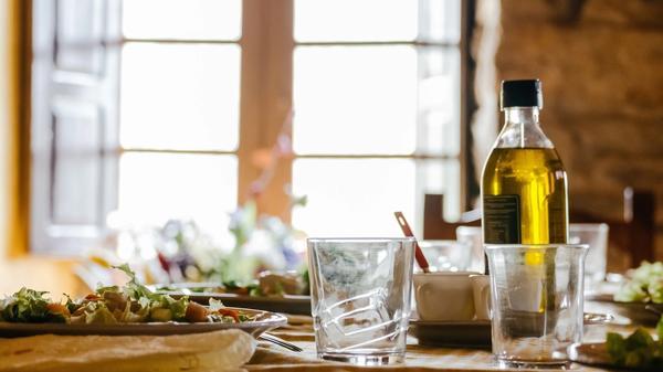 Olivenolje på ett spisebord med mat og glass rundt seg