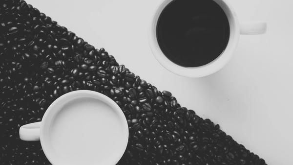 Bilde av en hvit kopp på svart bakgrunn og en svart kopp på hvit bakgrunn for å symbolisere Yin og Yang. Ilustrasjonsbilde tatt av Alex fra Unsplash
