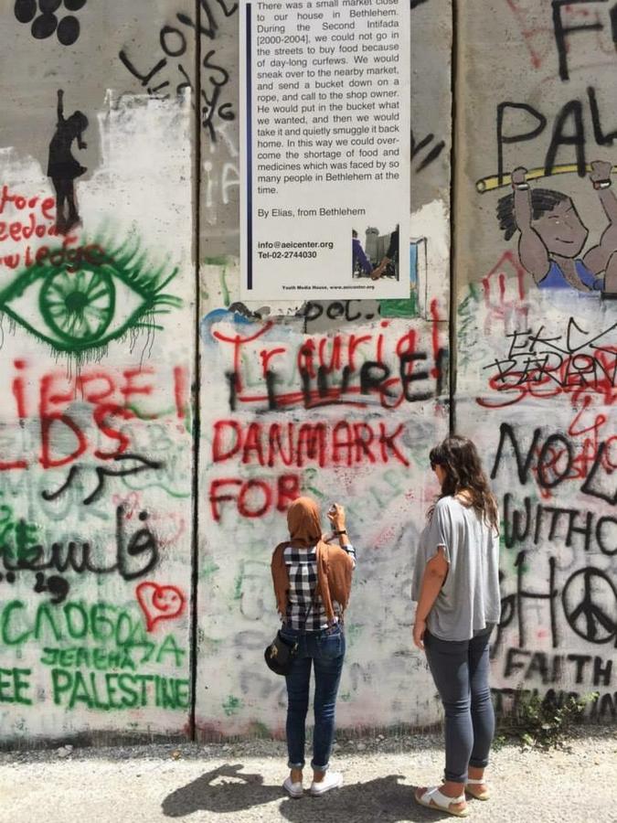 Bilde av to kvinner som står foran en vegg med graffiti (Foto privat)