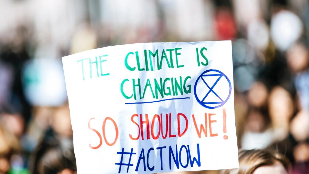 """Plakat i en demonstrasjon med følgende slagord: """"The Climate is Changing - So should we! #ACTNOW. Illustrasjonsbilde tatt av Markus Spiske fra Unsplash"""