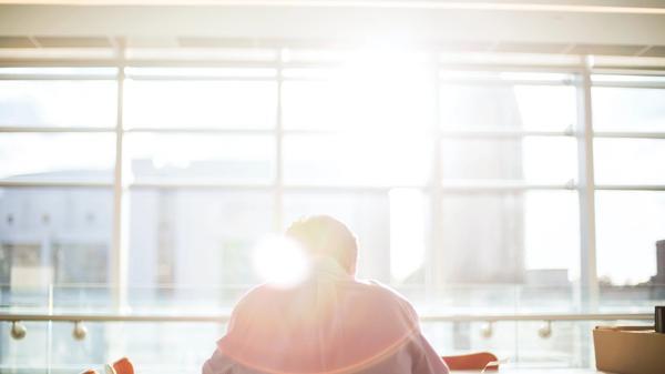 Illustrasjonsbilde av en mann som sitter å ser ut et stort vindu tatt av Bethany Legg fra Unsplash