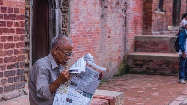 Illustrasjonsbilde av en eldre mann som sitter å leser avisen på en mursteinkant tatt av Aalok Atreya fra Unsplash