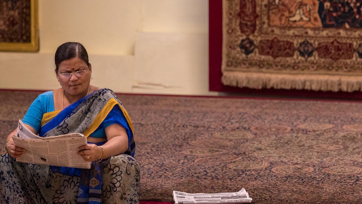 Indisk dame leser nyhetene på gangfeltet