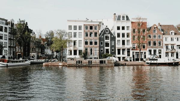 Bilde av Amsterdams karakteristiske murbygg, med kanalen i front.