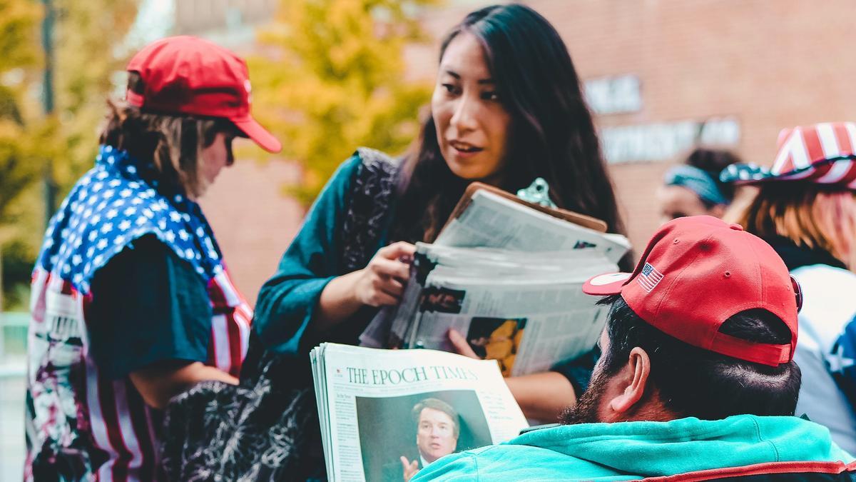 Kvinne holder en avis på gaten fremfor en mann som sitter og leser en avis