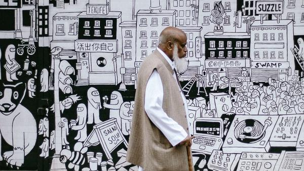 Mann med skjegg som går med en stokk forbi en vegg med tegning av en by. Illustrasjonsbilde tatt av Clem Onojeghuo fra Unsplash