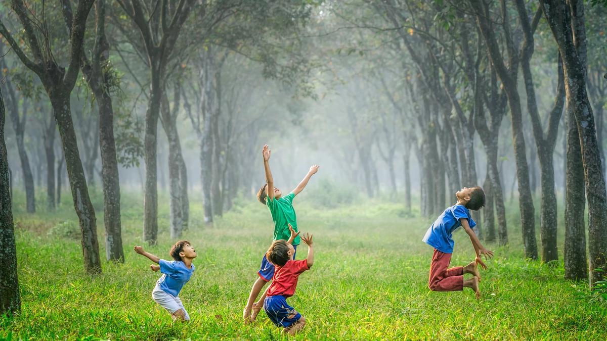 Illustrasjonsbilde av glade barn som leker i skogen tatt av Robert Collins fra Unsplash