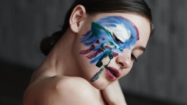 en kvinne omfavner seg selv med blå maling rundt øynet