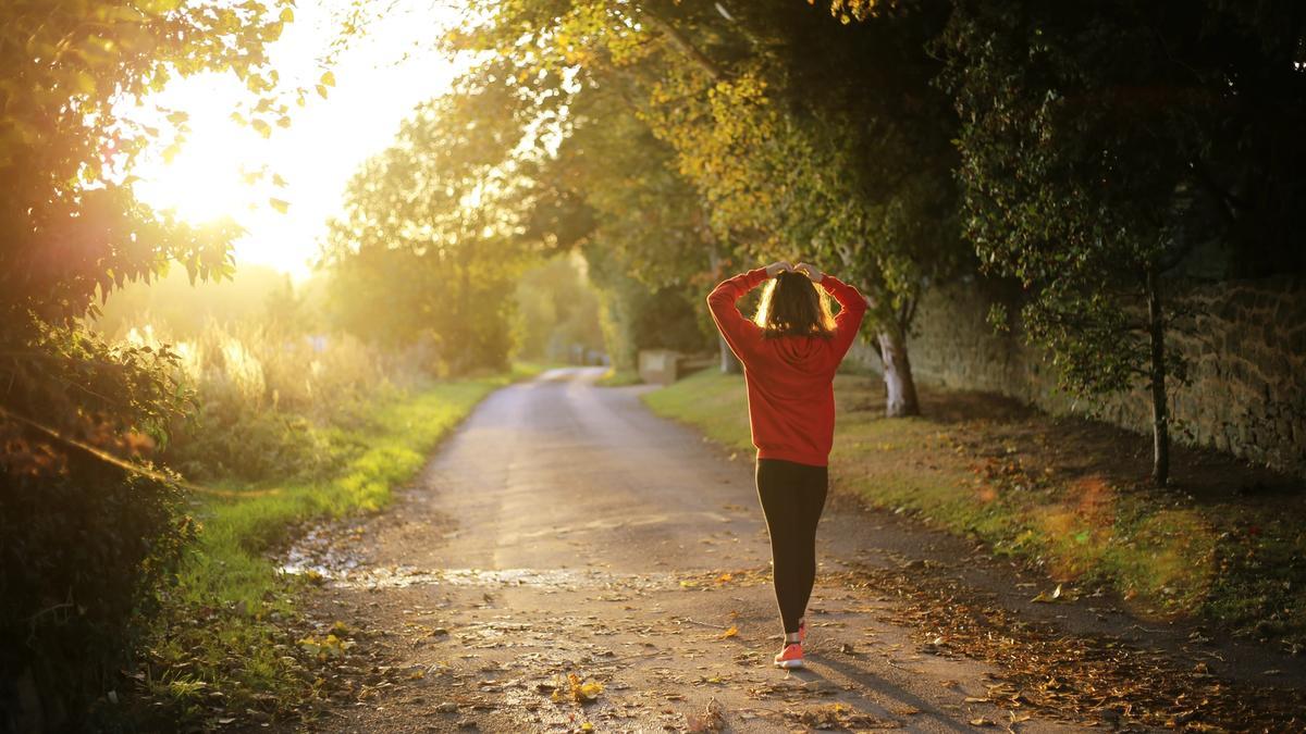 Illustrasjonsbilde av en kvinne med rød genser som går nedover en sti som er fylt med sollys med grønne trer rundt. Bildet er tatt av Emma Simpson fra Unsplash