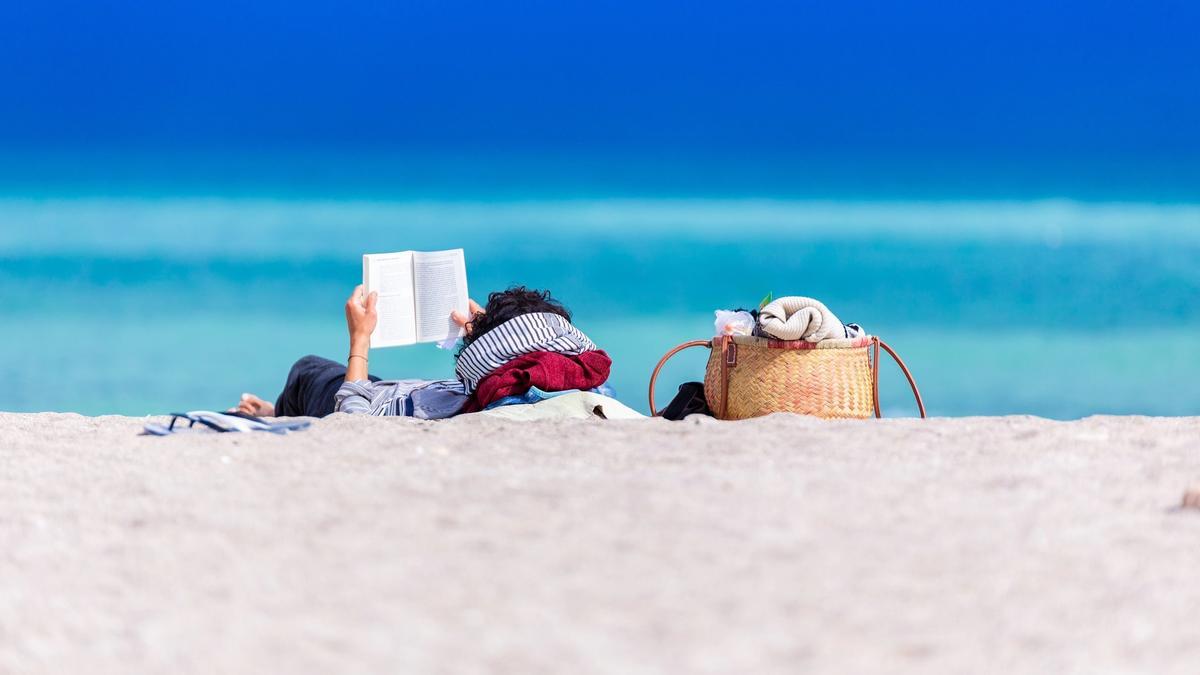 Illustrasjonsbilde av en person som ligger å leser en bok på en badestrand med blågrønt hav i bakgrunnen. Bildet tatt av Dan Dumitriu fra Unsplash