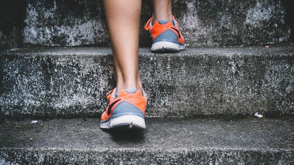 Illustrasjonsbilde av en person som går opp ei trapp med orange og grå joggesko tatt av Bruno Nascimento fra Unsplash