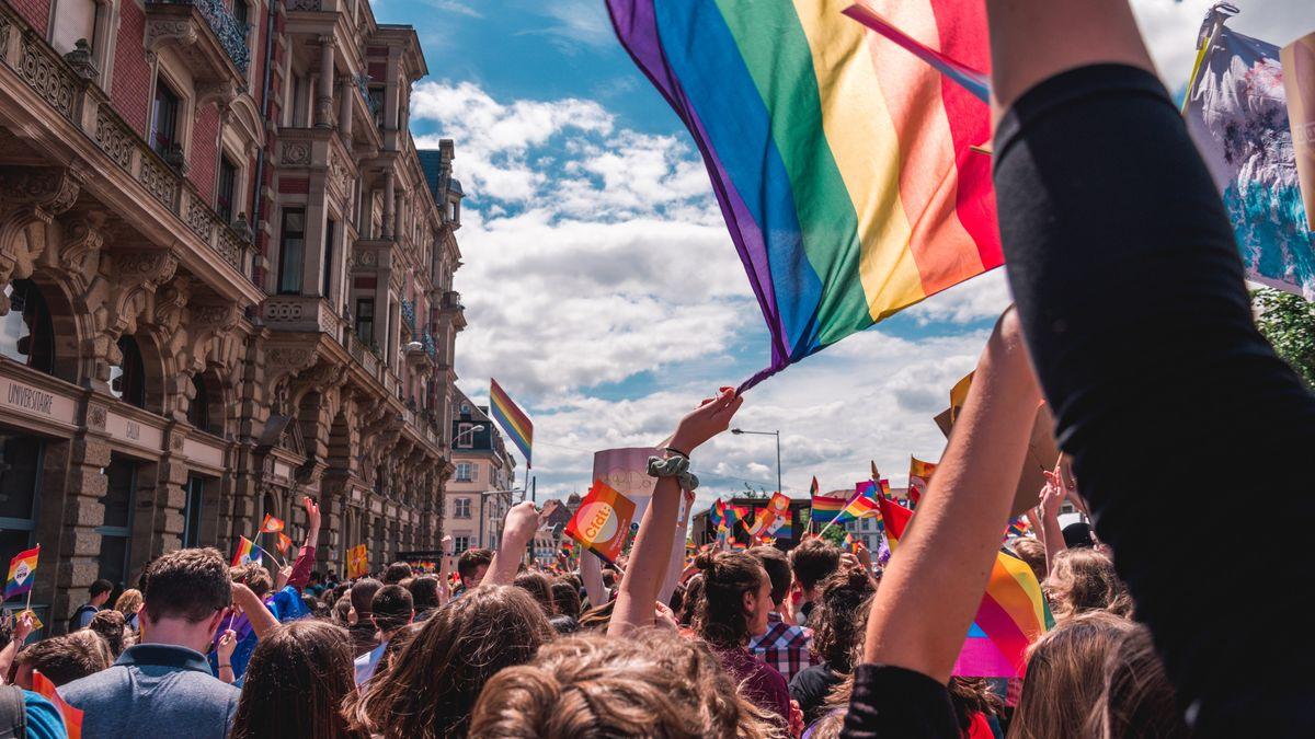 Mange mennesker som flagger med Pride-flagg