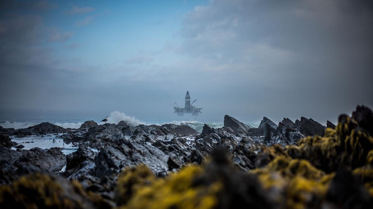Vilt hav med en oljerigg i det fjerne