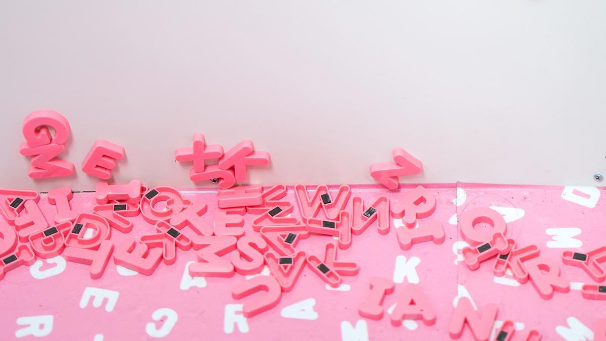 Rosa og hvite bokstaver som ligger rotete til på et hvit golv langs en hvit vegg. Illustrasjonsbilde tatt av Jason Leung fra Unsplash