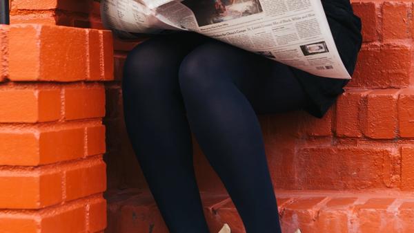 Illustrasjonsbilde av en kvinne som leser avisen tatt av The Creative Exchange fra Unsplash